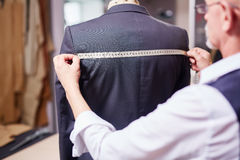 Tailor Measuring Garment in Atelier Stock Images