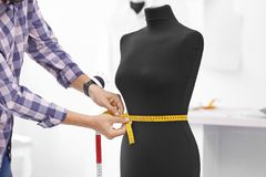 Tailor measuring mannequin in workshop. Closeup Stock Photography