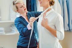 Tailor measuring woman to make her a bespoke shirt. Tailor measuring neck of women to make her a bespoke shirt royalty free stock photos