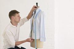 Tailor Measuring Shirt On Dressmaker's Model In Studio Stock Photo