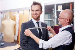 Tailor Measuring Smiling Client in Atelier. Portrait of handsome men smiling during model fitting of tailored suit in atelier Stock Photo