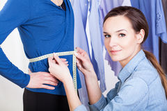 Tailor measuring a woman model Royalty Free Stock Photos