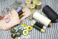 Tailor needles and threads. Composition with tailor needles and threads and buttons on fabric background Stock Photo