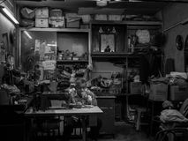 Tailor in Old Cramped Tailor Shop. A tailor sips tea in an old cramped shop stock photo