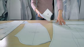 A tailor prepares several paper patterns. A woman arranges different tracing paper patterns on table stock footage