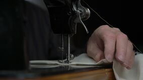 Tailor rotates handwheel and needle moves making seam