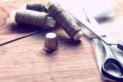 The tailor`s desk. Old sewing wooden drums or skeins on an old wooden worktable with scissors. Royalty Free Stock Photography