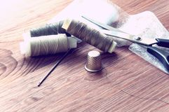 The tailor`s desk. Old sewing wooden drums or skeins on an old wooden worktable with scissors. Royalty Free Stock Photo