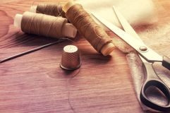 The tailor& x27;s desk. Old sewing wooden drums or skeins on an old wooden worktable with scissors. Toning for antiquity.  royalty free stock image