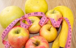 Tailor`s meter and fruit, apples, bananas, greyfruit. Chocolate or fruit diet. Choose a product for weight loss. Calorie count. Close-up. Healthy eating stock photography