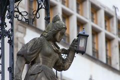 A detail of the Heinzelmännchen fountain. The tailor`s wife with a lantern, as she looks after the Heizelmännchen, thats helpful gnomes. The Fountain of Royalty Free Stock Images