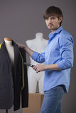 Tailor with scissors. Young fashion tailor with scissors and two mannequins royalty free stock image