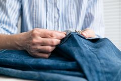 Tailor sew the hem of jeans in workshop. Close up view on hands with sewing needle stock photo