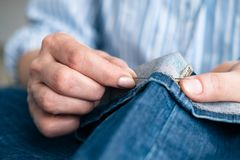 Tailor sew the hem of jeans in workshop. Close up view on hands with sewing needle royalty free stock photo