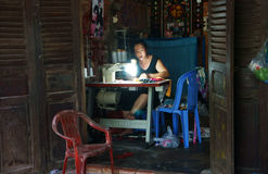 Tailor sewing clothing at home by sewing-machine