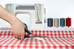Tailor. Sewing. Cutting fabric. Dressmaker at work. Fabric cutting scissors. Royalty Free Stock Image
