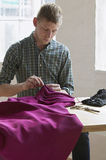 Tailor Sewing Fabric At Table In Studio Royalty Free Stock Photos