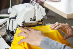 Tailor Sewing Fabric At Workbench. Cropped image of tailor sewing fabric at workbench in factory Stock Images