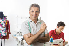 Tailor In Sewing Factory With Employee Working In Background Royalty Free Stock Photo