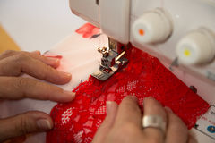 Tailor at sewing machine tailoring lingerie or a bra Stock Images