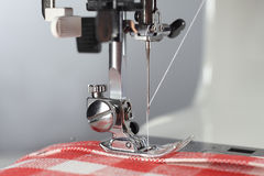 Tailor. Sewing machine working part with linen fabric in the red cell. Stock Photos