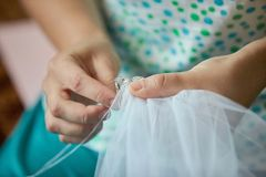 Tailor sewing the veil of a bride. Close up hands. stock image