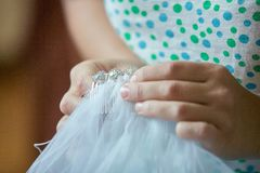 Tailor sewing the veil of a bride. Close up hands. royalty free stock photography
