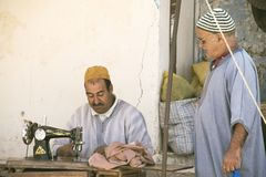 A tailor sews and talks with another man under a canopy at the local Berber market. Essaouira, Morocco - September 2017:  a tailor sews and talks with another Stock Images