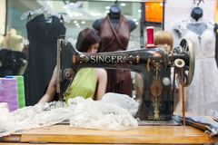 Tailor shop window featuring vintage Singer sewing machine with dresses and maniquins in background Brisbane Australia circa Septe royalty free stock photo