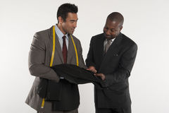 Tailor showing man a black suit Royalty Free Stock Images