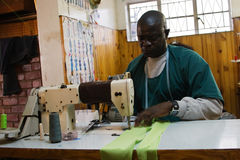 Tailor solutions. African American man working in a tailor workshop Royalty Free Stock Photography