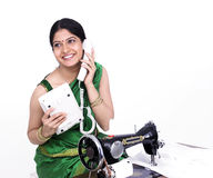 Tailor speaking on her phone Royalty Free Stock Photography