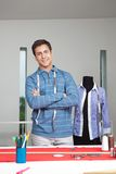 Tailor Standing Arms Crossed. Portrait of young male tailor standing arms crossed with mannequin in background Royalty Free Stock Photos