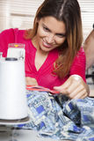 Tailor Stitching Fabric At Workbench. Smiling female tailor stitching fabric at workbench in factory Royalty Free Stock Image