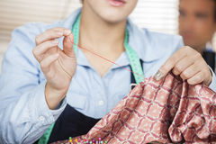 Tailor Stitching Textile In Sewing Factory. Midsection of female tailor stitching textile in sewing factory Stock Photography