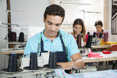 Tailor Stitching At Workbench In Sewing Factory. Young male tailor stitching at workbench in sewing factory with colleagues in background Royalty Free Stock Photos