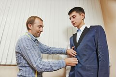 Tailor suit fitting. Male tailor designer make marks on a jacket during bespoke suit fitting Stock Photo