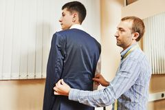 Tailor suit fitting. Male tailor designer make marks on a jacket during bespoke suit fitting stock image