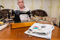 Tailor at the Table with Sewing Tools and Cloth Royalty Free Stock Photos