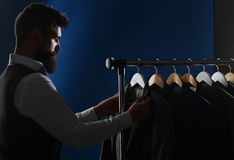 Tailor, tailoring. Men`s suit, tailor in his workshop. Elegant man`s suits hanging in a row. Luxury mens classic suits stock image
