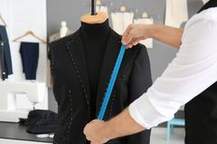 Tailor taking measurements of mannequin. In atelier Royalty Free Stock Image