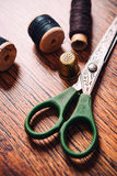 Tailor the tool to measure  length, scissors, spools of colored. Tailor the tool to measure the length,  scissors, spools of colored thread on a wooden Royalty Free Stock Images