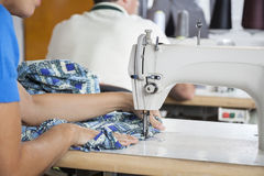 Tailor Using Sewing Machine At Workbench. Cropped image of female tailor using sewing machine at workbench in factory Royalty Free Stock Photo
