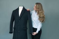 Tailor woman checking new sewn winter jacket on mannequin. royalty free stock image