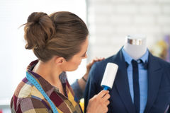 Tailor woman cleaning business suit. rear view Stock Image