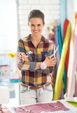Tailor woman with scissors and measuring tape. Portrait of smiling tailor woman with scissors and measuring tape royalty free stock image
