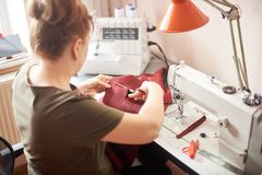 Tailor woman sitting on workplace in atelier and using scissors for cutting off cloth piece in sewing process. Back view. Woman sitting on her workplace in royalty free stock image