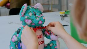 Tailor woman, toymaker tying bow on neck of teddy bear Royalty Free Stock Photography
