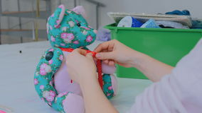 Tailor woman, toymaker tying bow on neck of teddy bear. At sewing studio. Handmade, craft and toy making concept. Close up shot stock footage
