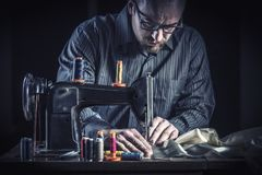 Work on clothes. Tailor work with sewing machine vintage style stock photography